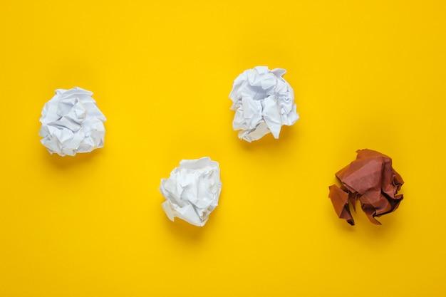 O conceito de singularidade, discriminação racial. bolas de papel amassado brancas e marrons na tabela amarela. vista superior, negócios de minimalismo Foto Premium