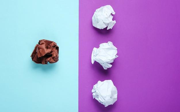 O conceito de singularidade, discriminação racial. bolas de papel amassado brancas e marrons na tabela azul roxa. negócio de minimalismo Foto Premium