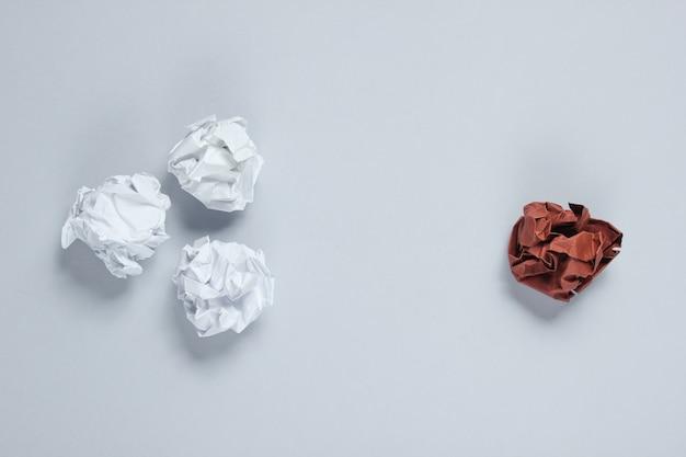 O conceito de singularidade, discriminação racial. bolas de papel amassado branco e marrom na mesa cinza. vista superior, minimalismo Foto Premium