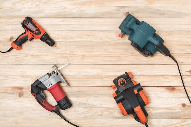 O conjunto de ferramentas elétricas de carpintaria de mão para madeira encontra-se sobre um fundo claro de madeira. Foto Premium