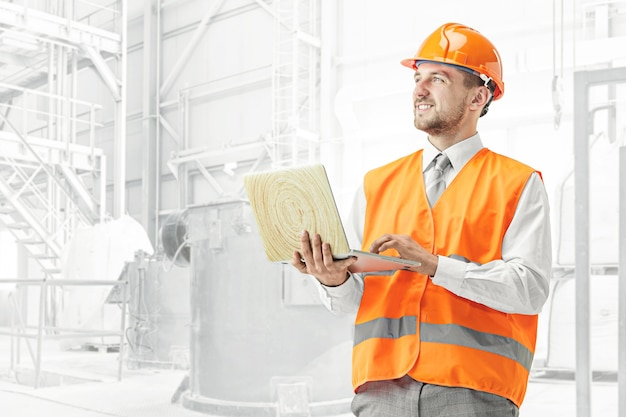 O construtor em capacete laranja contra industrial Foto gratuita