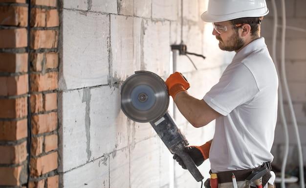 O construtor industrial trabalha com uma rebarbadora profissional para cortar tijolos e construir paredes interiores. eletricista. Foto gratuita