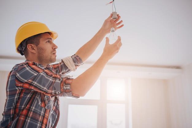 O construtor novo considerável em um capacete amarelo da construção está torcendo a ampola dentro. o homem está olhando para cima. Foto Premium