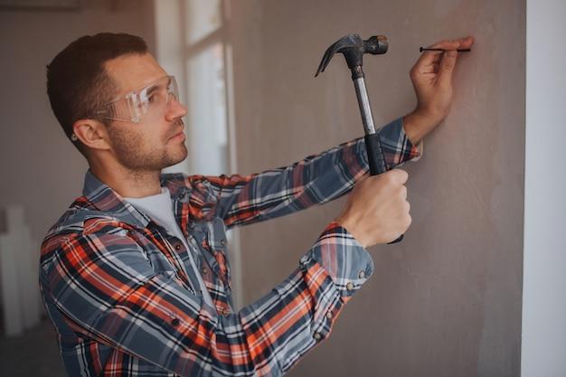 O construtor trabalha no canteiro de obras. trabalhador com balde e rolo de pintura perto da parede. Foto Premium