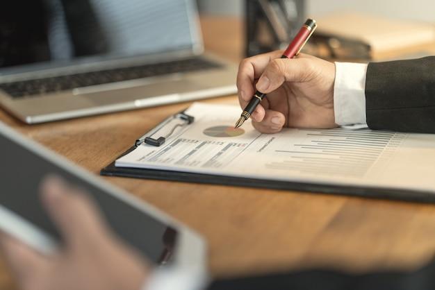 O contador que verifica documentos sobre gráfico e carta relacionando com relatórios financeiros e contabilidade de imposto da companhia Foto Premium