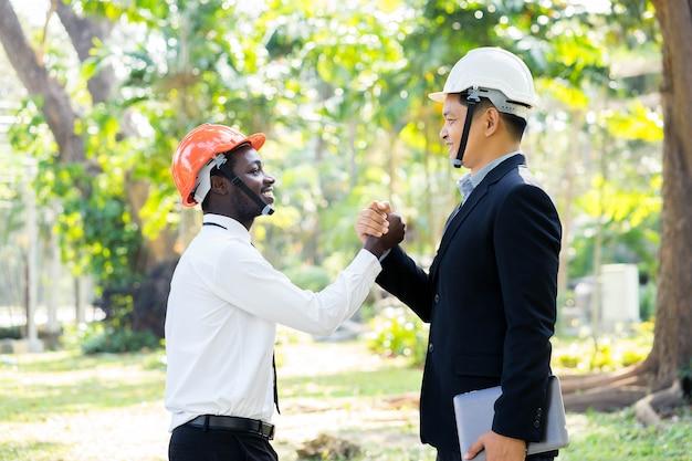 O coordenador asiático e africano do arquiteto agita as mãos com sorriso na natureza verde. Foto Premium