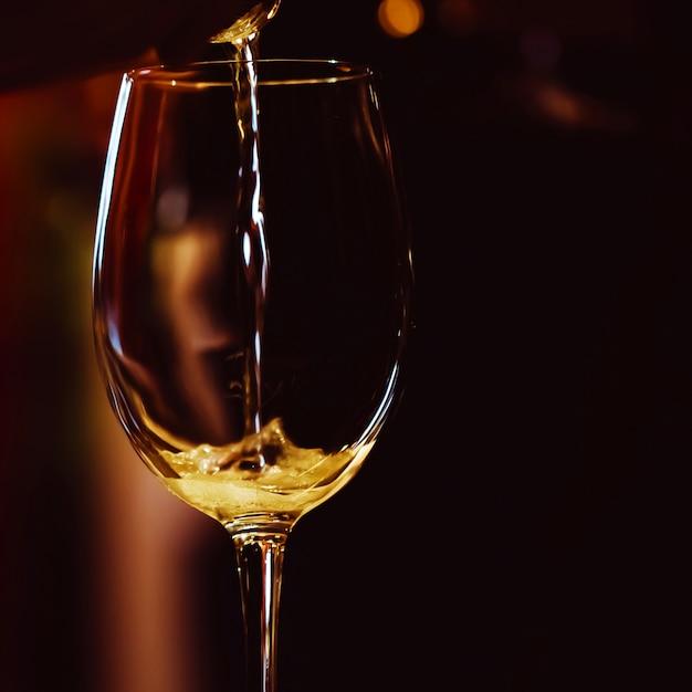 O copo de vinho iluminado está na mesa e uma gota de champanhe rosa é despejada nele Foto Premium