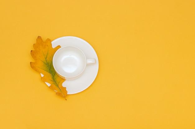 O copo vazio branco com pires e o carvalho do outono folheiam no fundo amarelo. Foto Premium