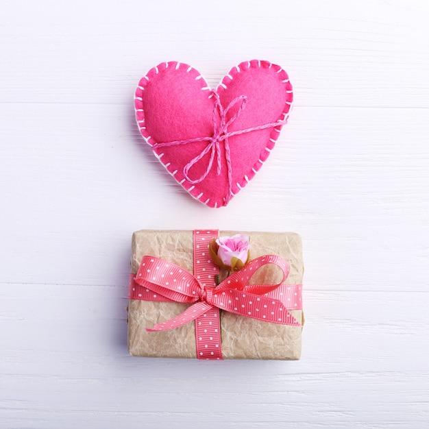 O coração de feltro do rosa e o presente feito a mão em uma tabela de madeira branca, conceito, bandeira, copiam o espaço. Foto Premium