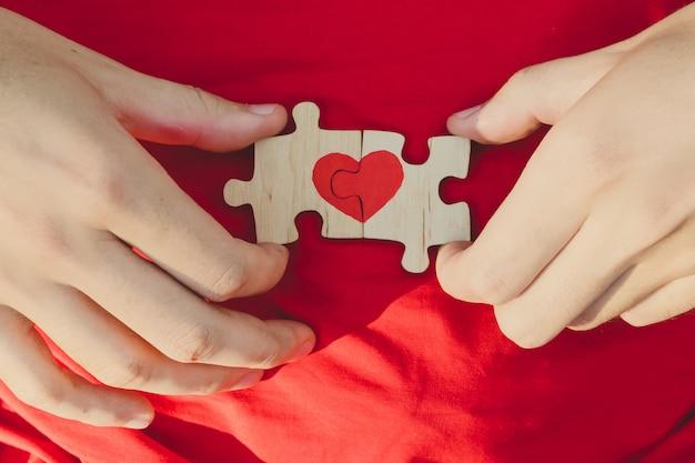 O coração vermelho é desenhado nas partes do enigma nas mãos masculinas no fundo vermelho. ame . dia dos namorados Foto Premium