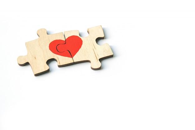 O coração vermelho é tirado nas partes do enigma de madeira que encontram-se próximos um do outro isolado no fundo branco. ame . são valentim. copie o espaço. Foto Premium