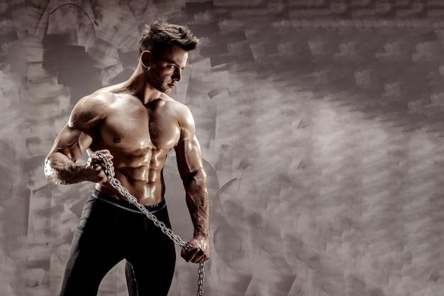 O corpo masculino perfeito - incrível fisiculturista posando. segure uma corrente com tatuagem Foto Premium