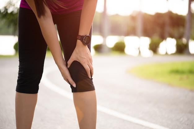 O corredor da mulher sente a dor em seu joelho no parque. Foto Premium