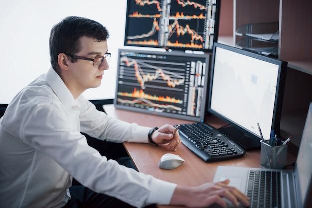 O corretor da bolsa está trabalhando em uma sala de monitoramento com telas. conceito do gráfico da finança dos estrangeiros de troca da bolsa de valores. empresários negociando ações on-line Foto gratuita
