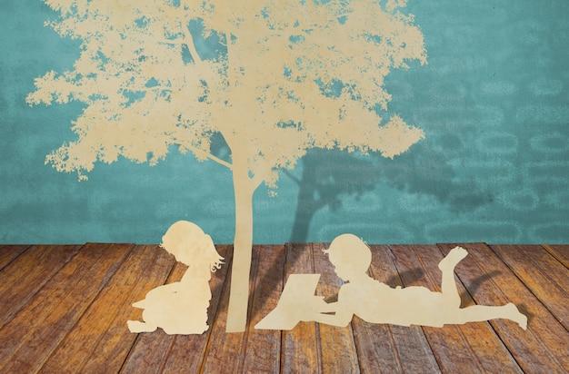 O corte do papel das crianças leu um livro sob a árvore Foto gratuita