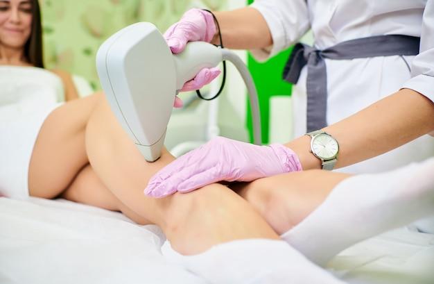 O cosmetologist do doutor conduz o procedimento da remoção do cabelo do laser do corpo de uma menina Foto Premium