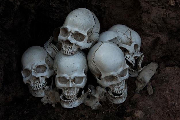 O crânio humano e pilha de ossos em fundo preto, a noite de halloween Foto Premium