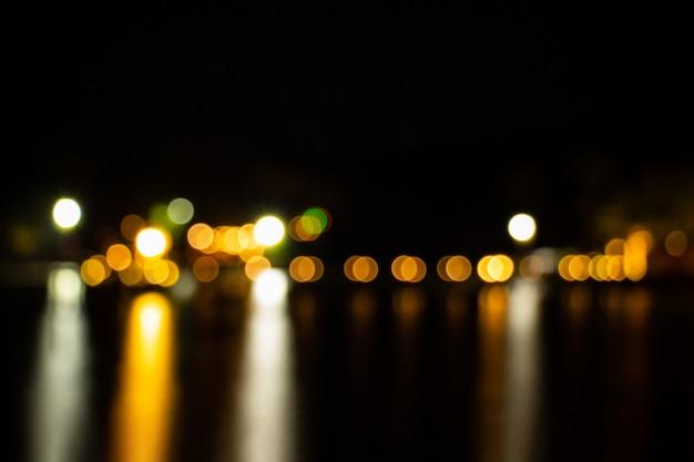 O crepúsculo da noite borrou o bokeh claro do ouro que reflete no fundo do sumário da água de superfície do mar. Foto Premium
