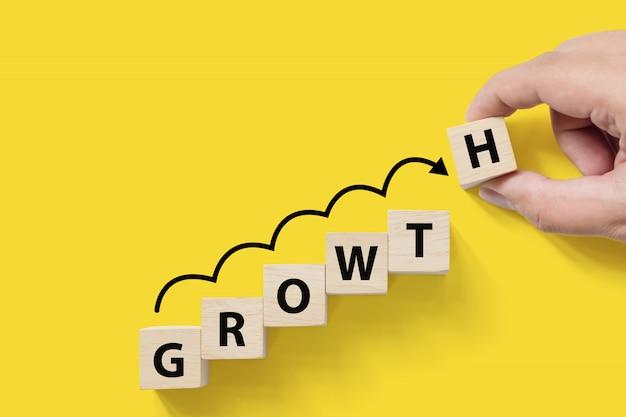 O crescimento crescente do sucesso de negócio aumenta acima o conceito. bloco de cubo arborizado com a palavra