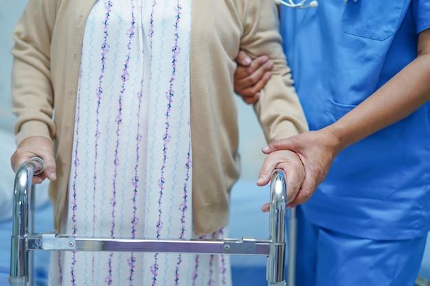 O cuidado asiático do doutor do fisioterapeuta da enfermeira, ajuda e apoia o paciente superior da mulher da senhora idosa. Foto Premium