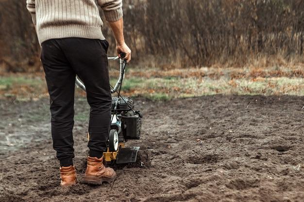 O cultivador solta o chão. Foto Premium