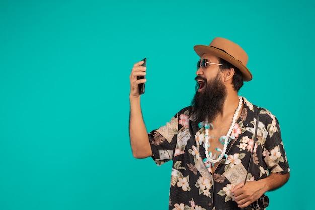 O de um homem de barba longa feliz usando um chapéu, vestindo uma camisa listrada, segurando um telefone em um azul. Foto gratuita