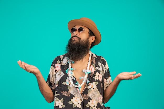 O de um homem feliz, com uma barba longa, usando um chapéu, vestindo uma camisa listrada, mostrando um gesto em um azul. Foto gratuita