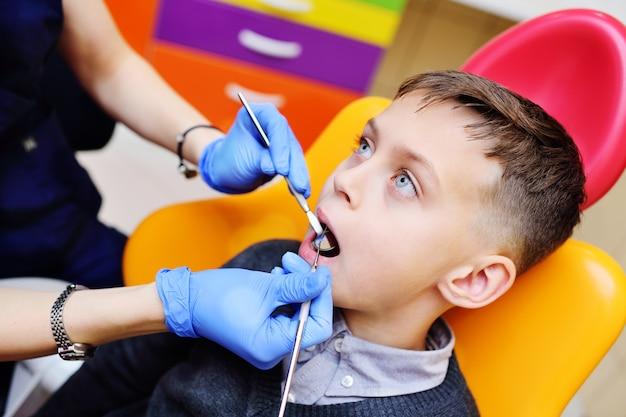 O dentista da mulher nova examina os dentes de um bebé que senta-se na cadeira dental. Foto Premium