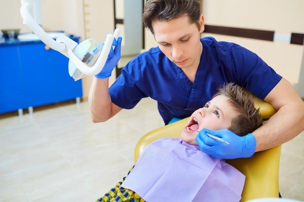 O dentista verificando os dentes do adolescente menino no consultório do dentista. Foto Premium