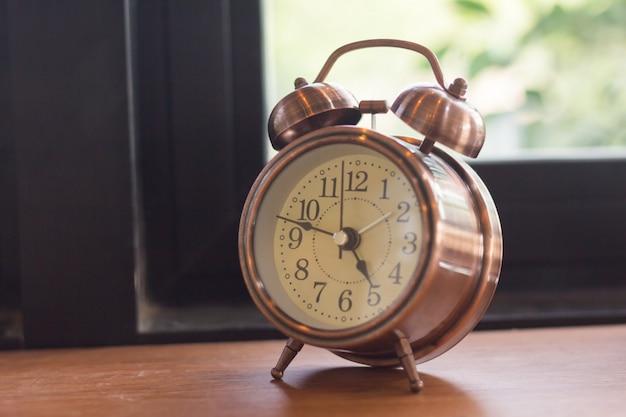 O despertador do foco seletivo é colocado no assoalho de madeira ao lado da janela. Foto Premium