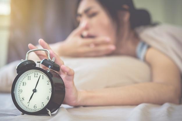 O despertador está tocando alto, com a mulher também sonolenta quando o fundo está embaçado. Foto Premium