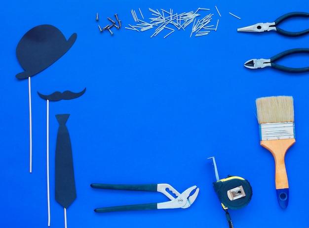 O dia de pai feliz e o laço e o chapéu coloridos das ferramentas no azul. Foto Premium