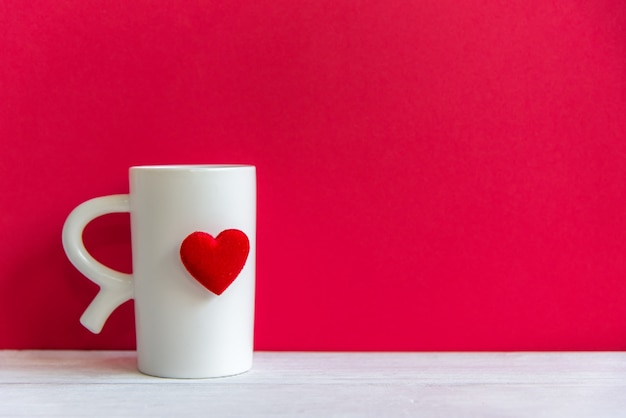 O dia dos namorados com coração branco do copo branco do café no copo, fundo vermelho da parede, copia o espaço valentine concept. Foto Premium