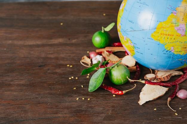 O dia mundial da alimentação, uma especiaria cheia de carros e cores frescas colocadas em um globo simulado em um piso de madeira marrom. Foto gratuita