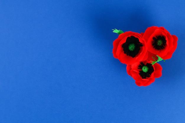 O dia vermelho de papel de anzac da papoila de diy, relembrança, recorda, papel crepom de memorial day no fundo azul. Foto Premium