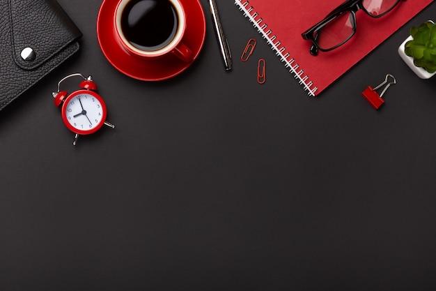 O diário vermelho da flor do despertador do bloco de notas do copo de café do fundo preto pontilha o teclado na tabela. vista superior com espaço para texto Foto Premium