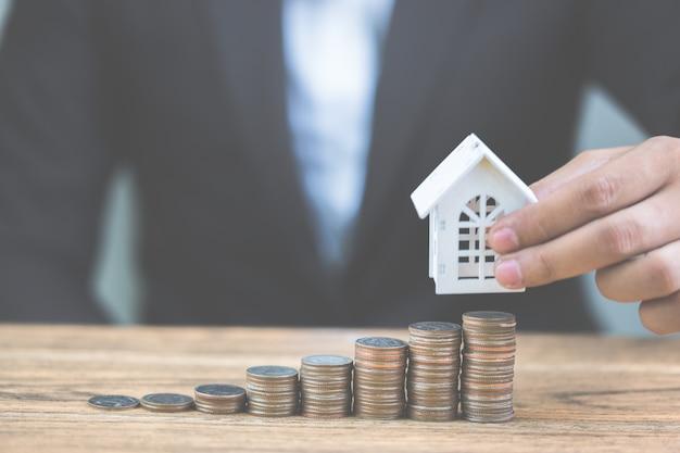 O dinheiro da pilha da moeda intensifica o crescimento crescente com a casa branca modelo na tabela de madeira. Foto Premium