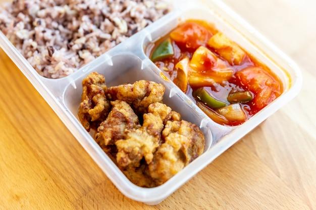 O doce e o ácido orgânicos denominados tailandeses fritaram com a baga da carne de porco e do arroz na caixa do produto comestível. Foto Premium