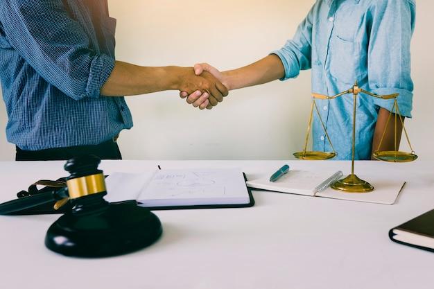 O dono da casa aperta as mãos com o advogado. plano de lei de moradias bem sucedido Foto Premium