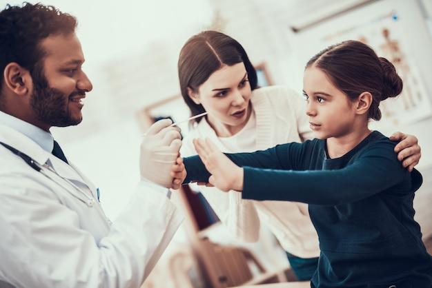 O doutor está examinando a garganta da menina mas a filha está recusando. Foto Premium