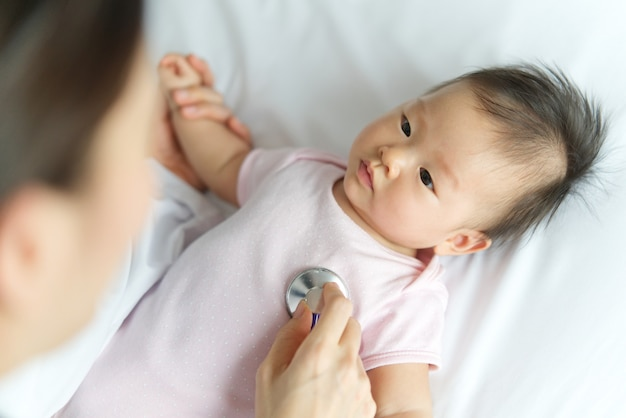 O doutor fêmea está escutando a taxa de pulso do coração do bebê recém-nascido asiático que sorri na cama usando o estetoscópio na sala. Foto Premium