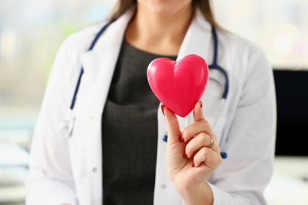 O doutor fêmea louro de sorriso bonito realiza no close up vermelho do coração do brinquedo dos braços. cardio terapeuta educação do aluno cpr 911 salvar vidas fazer médico medir a freqüência cardíaca cardíaca arritmia Foto Premium