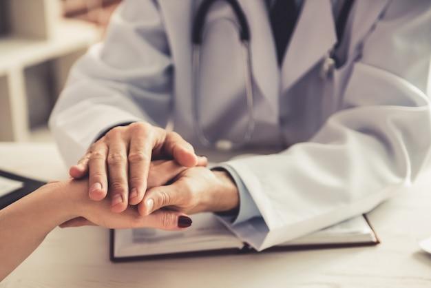 O doutor masculino acalma a menina paciente na clínica. Foto Premium