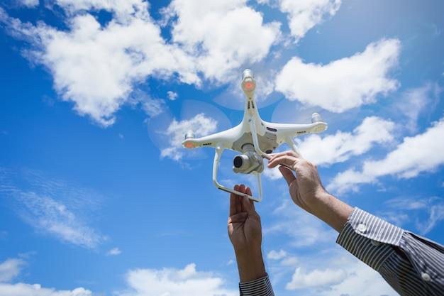 O drone e fotógrafo homem mãos o drone com a câmera profissional Foto Premium