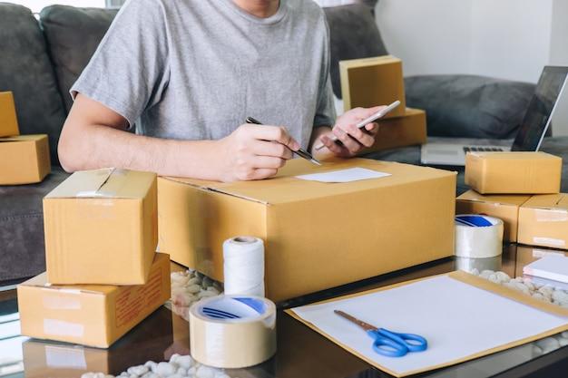 O empreendedor novo sme freelance recebe o cliente do pedido e toma nota que trabalha com o mercado em linha da entrega da caixa do tipo da embalagem no pedido de compra Foto Premium