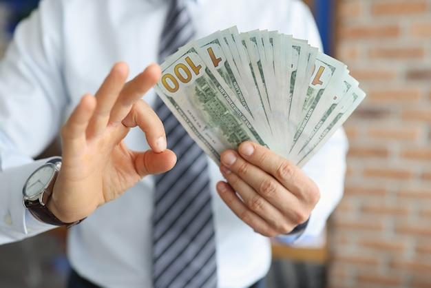 O empresário tem notas de cem dólares na mão com a segunda mão mostra o gesto ok. Foto Premium