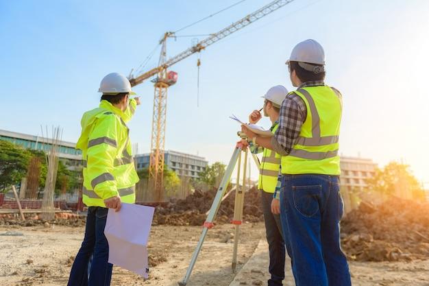O engenheiro civil inspeciona o trabalho usando comunicação via rádio com a equipe de gerenciamento na área de construção. Foto Premium