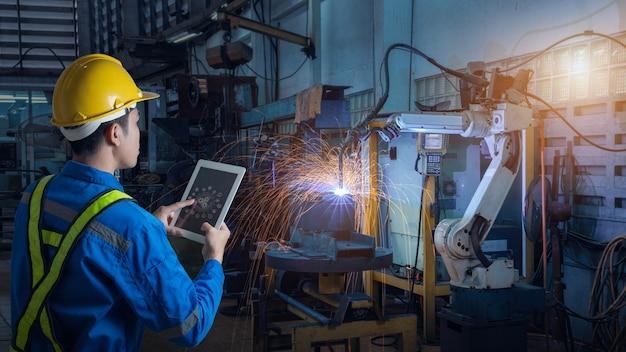 O engenheiro controla e verifica a robótica de soldagem automática de armas na fábrica inteligente Foto Premium