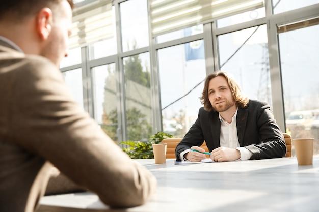 O entrevistador está questionando um candidato em uma entrevista de emprego. Foto Premium