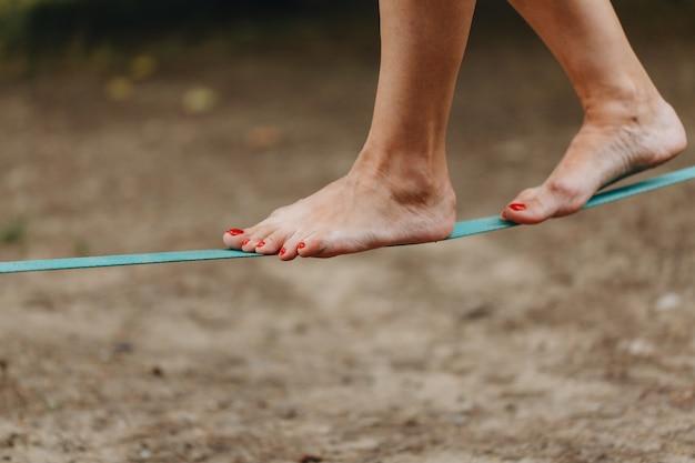 O equilibrista na corda-bamba usa uma tipoia apertada que é fixada nas árvores a baixa altitude. Foto Premium